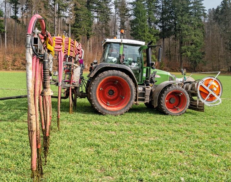 Der Fendt 412 Vario mit 15 Meter Schleppschlauchverteiler beim Güllen eines Gerstenfeldes.