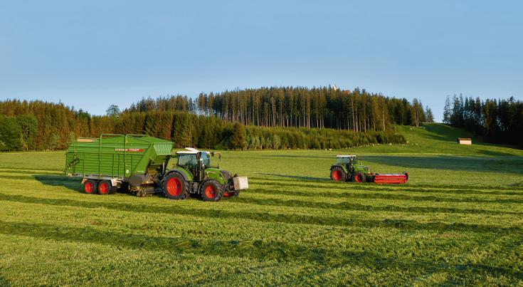 Fendt 313 Vario med Fendt Tigo MR 50 Profi arbejder på græsmark.